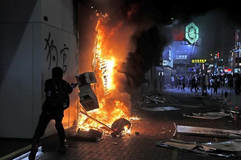 Protesters set fire to a Xiaomi shop at Nathan road in Hong Kong, Sunday, Oct. 20, 2019. Hong Kong protesters again flooded streets on Sunday, ignoring a police ban on the rally and setting up barricades amid tear gas and firebombs. (AP Photo/Kin Cheung)