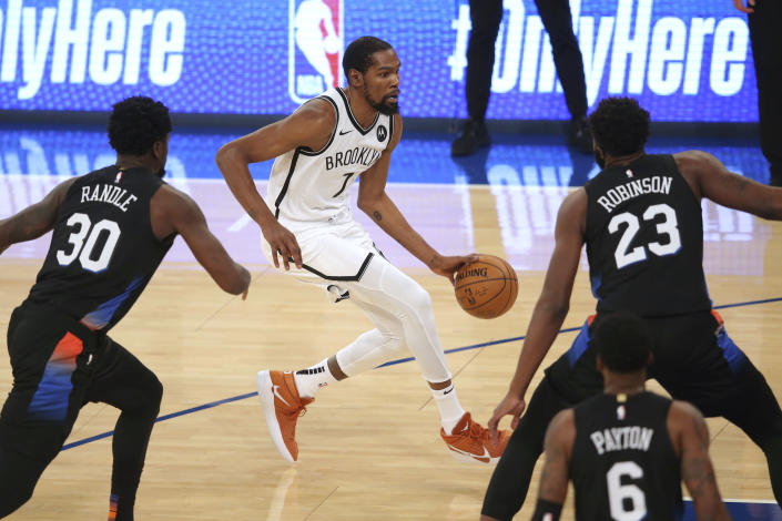 Brooklyn Nets forward Kevin Durant (7) dribbles the ball as New York Knicks forward Julius Randle (30) and center Mitchell Robinson (23) defend during the first quarter of an NBA basketball game Wednesday, Jan. 13, 2021, in New York. (Brad Penner/Pool Photo via AP)