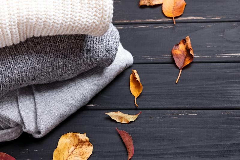 Cozy sweaters and autumn leaves on thw black wooden background