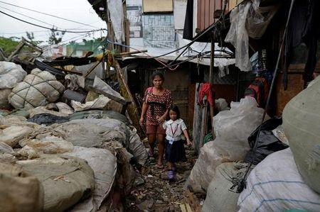 "Weng Ruda, 36, mother of three walks her daughter to school at a slum area in Quezon city, Metro Manila, Philippines October 13, 2016.  ""I like that he is very tough. There are no children loitering around now. They also avoid picking up bad habits,"" she said. REUTERS/Ezra Acayan"
