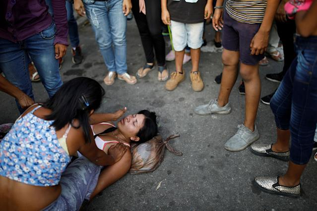 <p>A relative of inmates at the General Command of the Carabobo Police faints outside the prison, where a fire occurred in the cells area, according to local media, in Valencia, Venezuela, March 28, 2018. (Photo: Carlos Garcia Rawlins/Reuters) </p>
