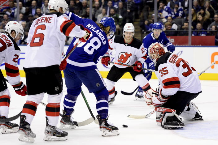 New Jersey Devils goaltender Cory Schneider (35) keeps his eye on a loose puck as Maple Leafs right wing William Nylander (88) looks for the shot under pressure from New Jersey Devils' Andy Greene (6), Damon Severson (28) and Blake Coleman (20) during the second period of an NHL hockey game Tuesday, Jan. 14, 2020, in Toronto. (Frank Gunn/The Canadian Press via AP)