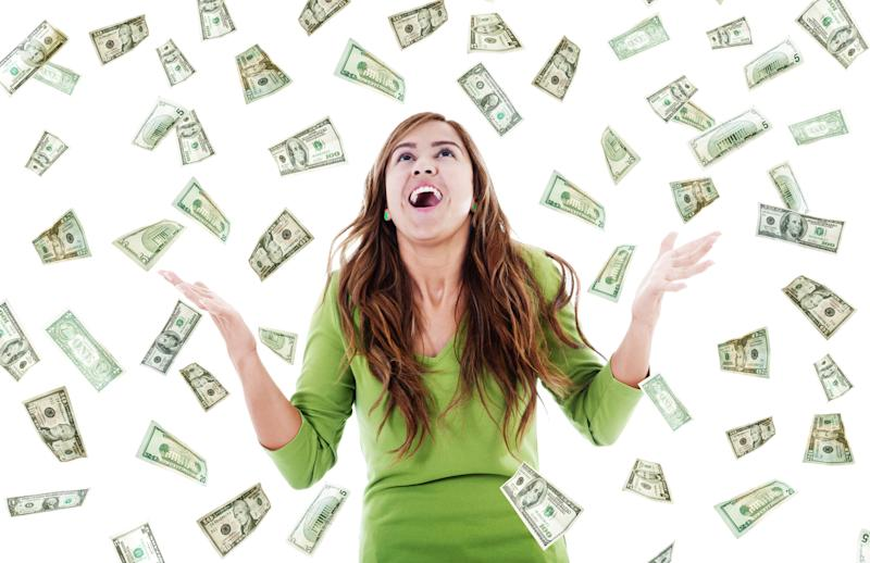 A happy young woman in a green shirt looking up as lots of U.S. currency floats down around her from the sky.