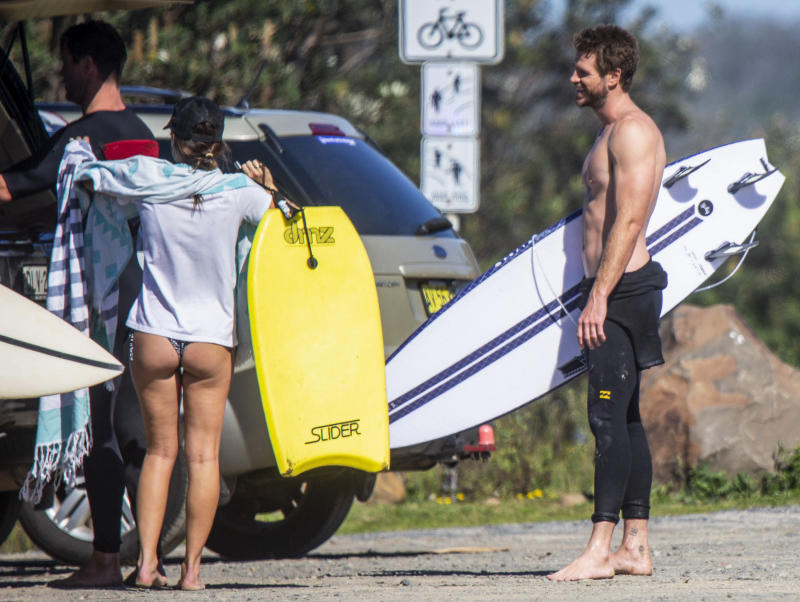 Liam Hemsworth holds on to his surfboard in Byron Bay
