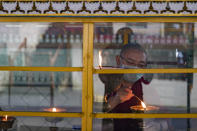 An exile Tibetan Buddhist monk wears a face mask as a precautionary measure against the coronavirus as he lights a ceremonial butter lamp in Dharmsala, India, Friday, Sept. 11, 2020. India's coronavirus cases are now the second-highest in the world and only behind the United States. (AP Photo/Ashwini Bhatia)