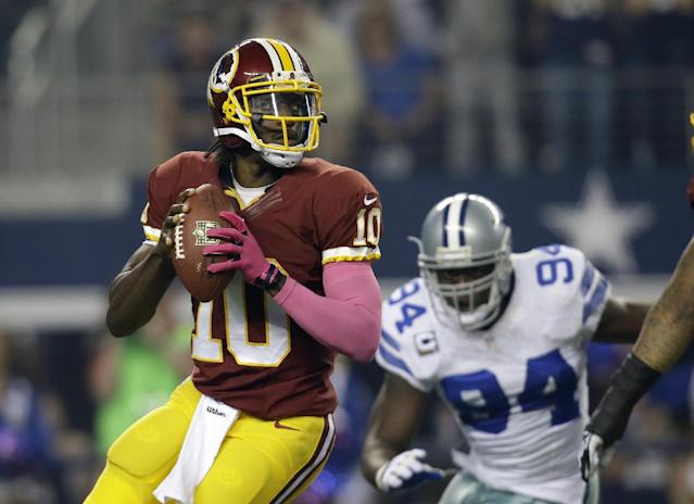 Washington Redskins quarterback Robert Griffin III (10) prepares to pass as Dallas Cowboys defensive end DeMarcus Ware (94) defends in the first half of an NFL football game, Sunday, Oct. 13, 2013, in Arlington, Texas. (AP Photo/Tim Sharp)