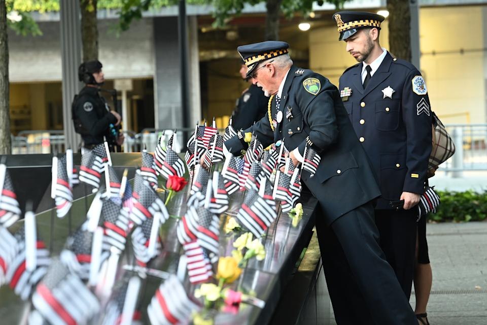NEW YORK, NEW YORK - SEPTEMBER 11: Retired Willow Springs, IL Chief Sam Pulia and his nephew, Chicago Police Sgt. Daniel Pulia place flags at the South Tower before a ceremony at the National September 11 Memorial & Museum commemorating the 20th anniversary of the September 11th terrorist attacks on the World Trade Center on September 11, 2021 in New York City. The nation is marking the 20th anniversary of the terror attacks of September 11, 2001, when the terrorist group al-Qaeda flew hijacked airplanes into the World Trade Center, Shanksville, PA, and the Pentagon, killing nearly 3,000 people. (Photo by David Handschuh-Pool/Getty Images)