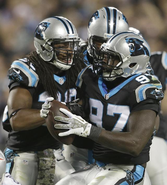 Carolina Panthers' Mario Addison (97) celebrates his fumble recovery with teammates during the first half of an NFL football game against the New England Patriots in Charlotte, N.C., Monday, Nov. 18, 2013. (AP Photo/Gerry Broome)