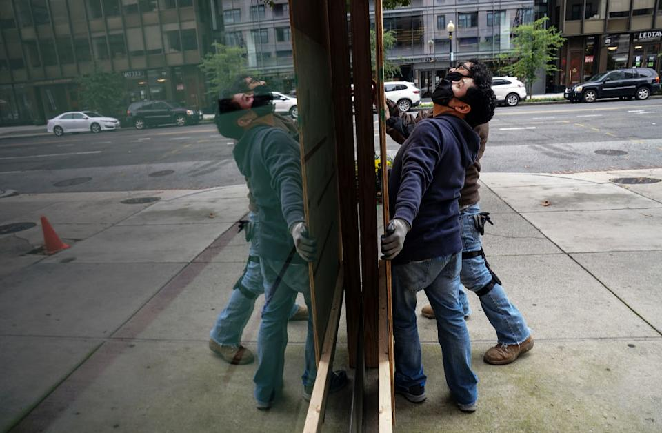 Workers use plywood to cover the glass windows in Washington DC.