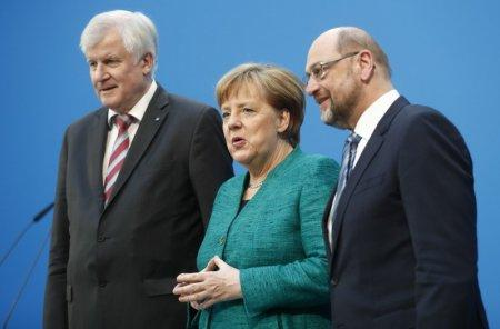 Christian Democratic Union (CDU) leader and German Chancellor Angela Merkel, Christian Social Union (CSU) leader Horst Seehofer and Social Democratic Party (SPD) leader Martin Schulz pose after a statement on coalition talks to form a new coalition government in Berlin, Germany, February 7, 2018. REUTERS/Hannibal Hanschke