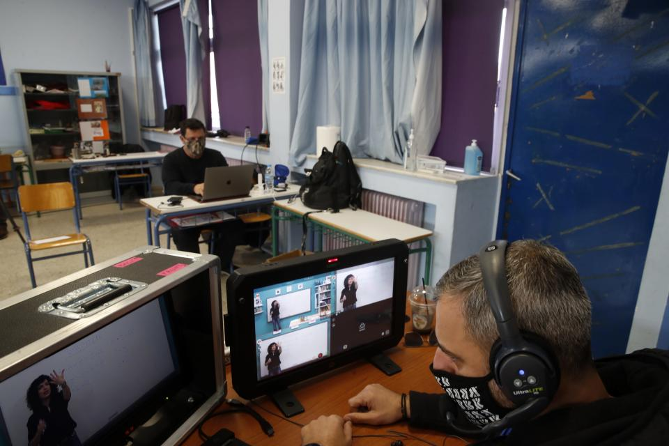 A director watches the monitors as teacher Rania Koukli records lessons that are broadcast on public television, at an elementary school in Athens, Wednesday, Nov. 18, 2020. Most other European countries have vowed to keep schools open, but the pandemic has hit Greece hard for the first time in recent weeks following a successful lockdown in the spring, overwhelming hospitals in parts of the country. State television is making and broadcasting lessons, while teachers sit in empty classrooms talking to remote students. Despite some problems, they say it keeps children in touch with their schools. (AP Photo/Thanassis Stavrakis)