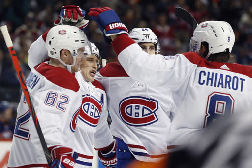 Montreal Canadiens right wing Brendan Gallagher, second from left, celebrates with teammates after scoring a goal during the first period of an NHL hockey game against the New York Islanders, Tuesday, March 3, 2020, in New York. From left are Montreal Canadiens left wing Artturi Lehkonen (62), center Phillip Danault (24) and defenseman Ben Chiarot (8). (AP Photo/Kathy Willens)