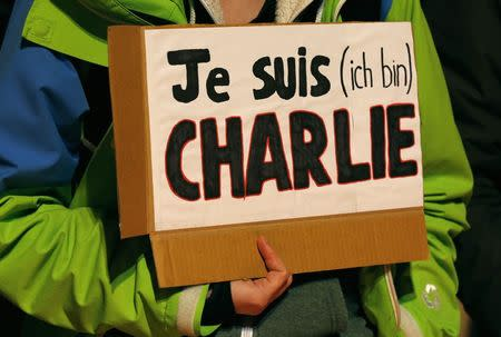 """A woman holds a placard which reads """"I am Charlie"""" to pay tribute to victims, in front of the Brandenburg Gate near the French embassy at Pariser Platz in Berlin January 7, 2015, following a shooting by gunmen at the offices of weekly satirical magazine Charlie Hebdo in Paris. REUTERS/Fabrizio Bensch"""