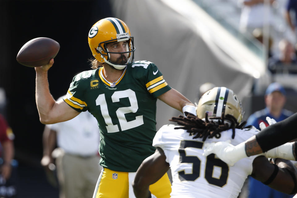 Green Bay Packers quarterback Aaron Rodgers (12) throws a pass as New Orleans Saints outside linebacker Demario Davis (56) rushes during the first half of an NFL football game, Sunday, Sept. 12, 2021, in Jacksonville, Fla. (AP Photo/Stephen B. Morton)