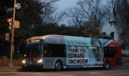 A Washington Metro bus is seen with an Edward Snowden sign on its side panel