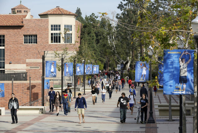FILE - In this Feb. 26, 2015, file photo, students walk on the University of California, Los Angeles campus. Xiaoning Sui, 48, of Surrey, British Columbia, is accused of paying $400,000 to get her son into the University of California, Los Angeles, as a fake soccer recruit. She has become the 52nd person charged in a sweeping college admissions bribery scheme, according to an indictment unsealed Tuesday, Sept. 17, 2019, in Boston's federal court. (AP Photo/Damian Dovarganes, File)