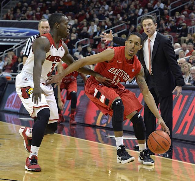 Hartford's Yolonzo Moore II, right, attempts to drive around the defense of Louisville's Chris Jones during first half action of their NCAA mens college basketball game Nov. 19, 2013, in Louisville, Ky. (AP Photo/Timothy D. Easley)