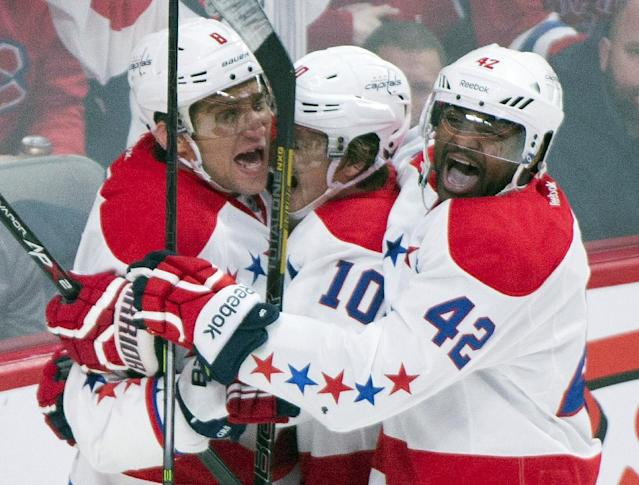Washington Capitals' Alex Ovechkin, left, celebrates with teammates Martin Erat, center, and Joel Ward after Ovechkin scored against the Montreal Canadiens during the second period of an NHL hockey game in Montreal, Saturday, Jan. 25, 2014. (AP Photo/The Canadian Press, Graham Hughes)
