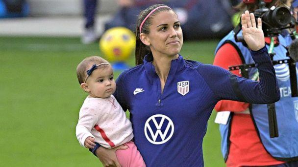 PHOTO: United States forward Alex Morgan waves to fans in the stands while holding her daughter Charlie Elena Carrasco after a SheBelieves Cup women's soccer match against Brazil, Feb. 21, 2021, in Orlando, Fla. (Phelan M. Ebenhack/AP)