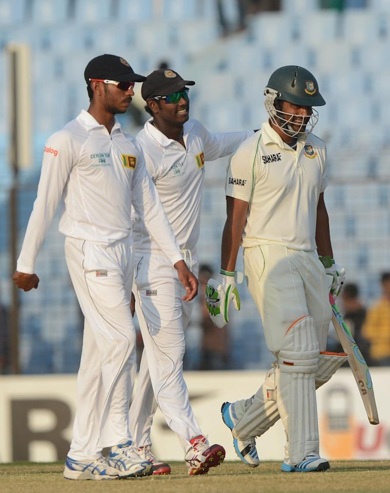 Bangladesh batsman Tamim Iqbal (R) and Sri Lankan cricket captain Angelo Mathews (C) and fielder Kithuruwan Vithanage (L) walk off the field after the fourth day of the second Test match between Bangladesh and Sri Lanka at The Zahur Ahmed Chowdhury Stadium in Chittagong on February 7, 2014. AFP PHOTO/ Munir uz ZAMAN