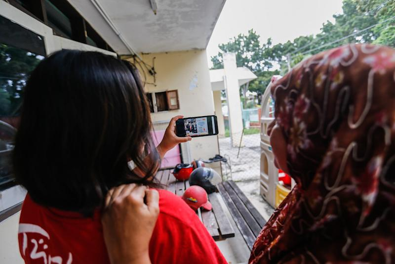 Noor Wahida Baba Din and her daughter Nur Dhamirah Lee watch the Budget 2020 speech by Finance Minister Lim Guan Eng 'live' on the phone at home in Bukit Gelugor October 11, 2019. — Picture by Sayuti Zainudin