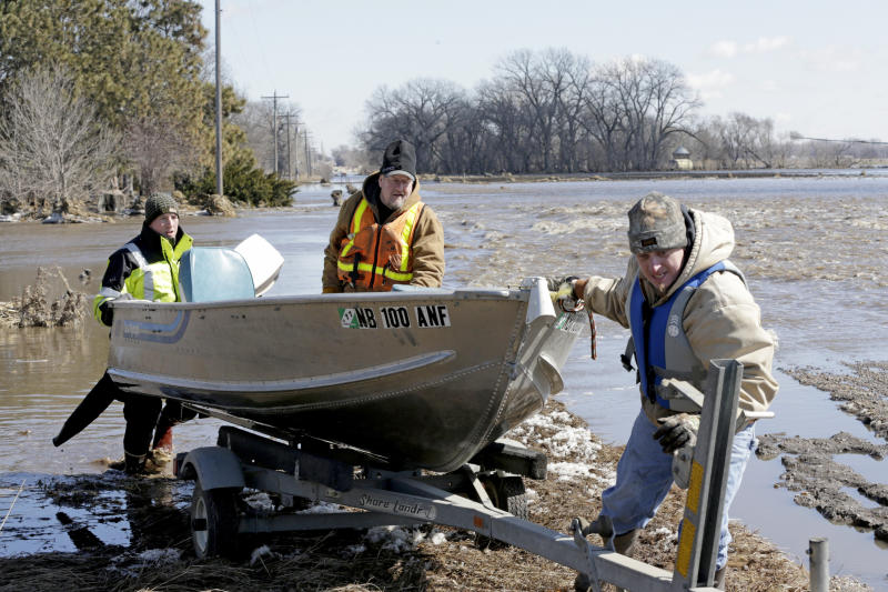 RETRANSMISSION TO CORRECT SURNAME- Tom Wilke center his son Chad right and Nick Kenny load a boat out of the swollen waters of the North Fork of the Elkhorn River after checking on the Witke's flooded property in Norfolk Neb. Friday March 1