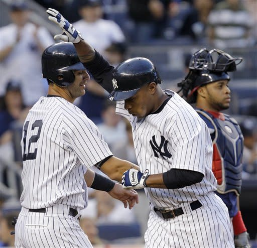 New York Yankees' Dewayne Wise, right, celebrates with Eric Chavez after hitting a second-inning, two-run home run during a baseball game at Yankee Stadium in New York, Monday, June 25, 2012. Cleveland Indians catcher Carlos Santana is at rear. (AP Photo/Kathy Willens)