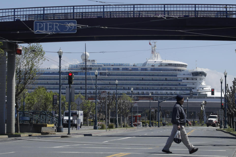 FILE - In this April 7, 2020, file photo, a man crosses the street under a pedestrian bridge at Pier 39 as the Grand Princess cruise ship, rear, is shown docked at Pier 35 in San Francisco. Cruise ships are returning to San Francisco after a 19-month hiatus brought on by the pandemic in what's sure to be a boost to the city's economy, the mayor announced Friday, Oct. 8, 2021. (AP Photo/Jeff Chiu, File)