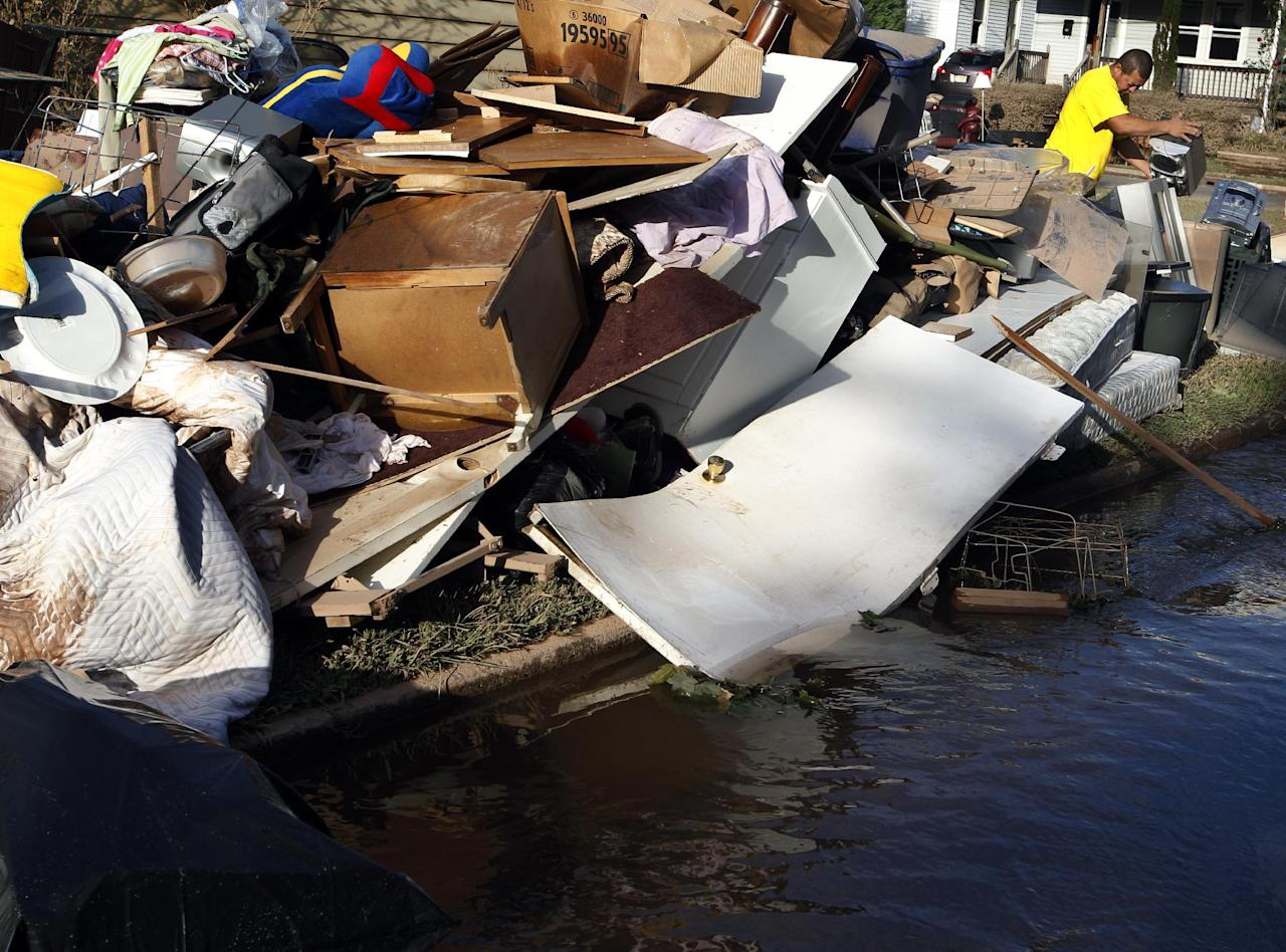 Johnny Lamca throws away ruined items from his flooded home in Manville, N.J., Monday, Aug. 29, 2011. Lamca said this flooding from Hurricane Irene was the worst of the four times that his home has been flooded by the Raritan River. Earlier Monday in Manville, Gov. Chris Christie said waters had reached or passed record levels at nine river locations, and he warned that the Passaic River had not yet crested. (AP Photo/Mel Evans)