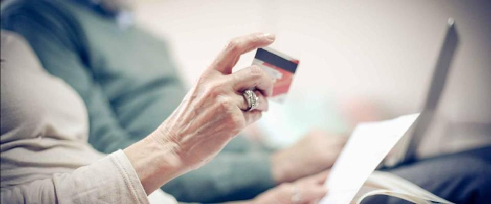 Senior couple at home checking finance on credit card.