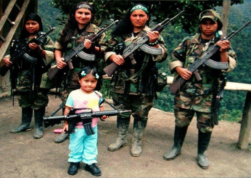 FARC rebels pose with an unidentified girl holding a weapon in southern Colombia in this undated photo confiscated by the Colombian police and released to the media on November 12, 2009. REUTERS/National Police/Handout