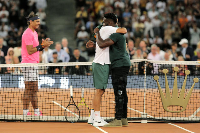 Springbok Captain Siya Kolisi, right, greets Roger Federer while Rafael Nadal looks on ahead of their exhibition tennis match held at the Cape Town Stadium in Cape Town, South Africa, Friday Feb. 7, 2020. (AP Photo/Halden Krog)