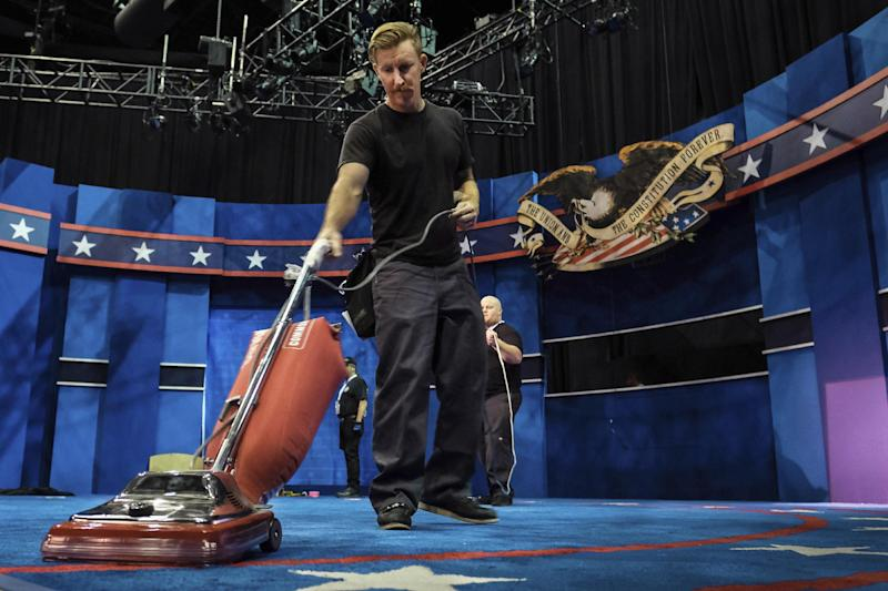 A stagehand vacuums the carpet as preparations continue Monday, Oct. 17, 2016 at the University of Nevada, Las Vegas in Las Vegas for the final debate between Democratic presidential nominee Hillary Clinton and Republican presidential nominee Donald Trump on Wednesday. (AP Photo/J. David Ake)