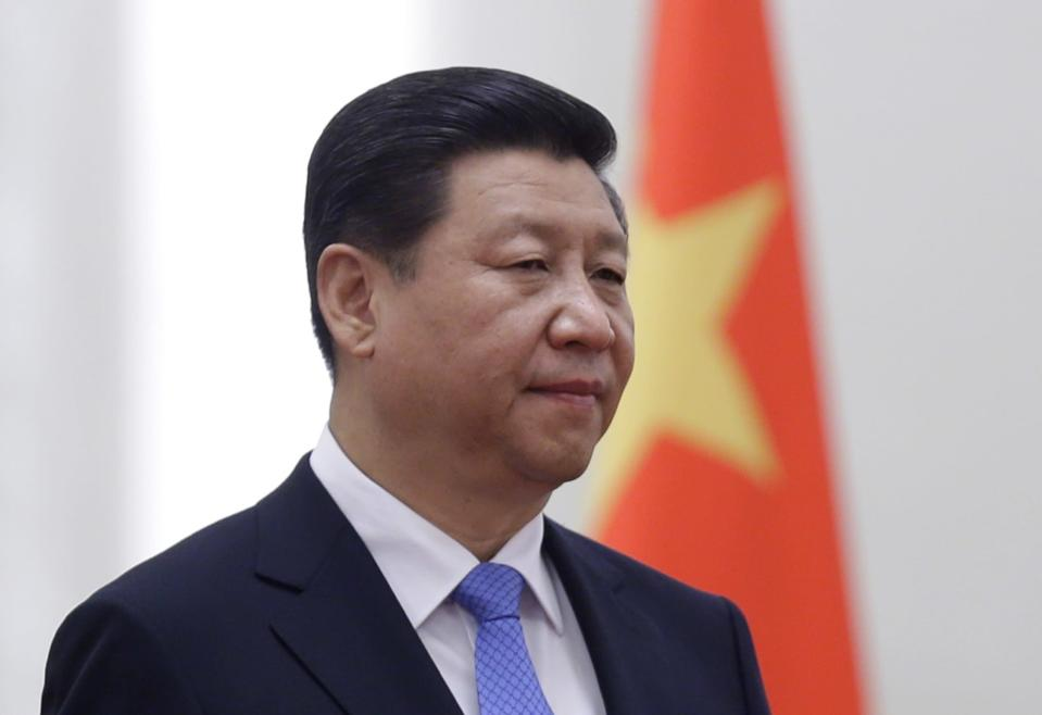 """China's President Xi Jinping stands next to a Chinese national flag during a welcoming ceremony at the Great Hall of the People, in Beijing, November 13, 2013. Unimpressed by the promotion of markets to a """"decisive"""" role in China's reform agenda for the next decade, investors sold off Chinese shares on Wednesday, disappointed by a lack of details in the reform plan and apparent reluctance to overhaul the state-owned sector. REUTERS/Jason Lee (CHINA - Tags: POLITICS BUSINESS)"""