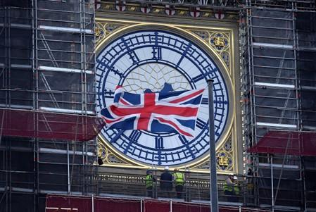 A Union Jack flag flutters in front of Big Ben as workers inspect one of its clocks, in London