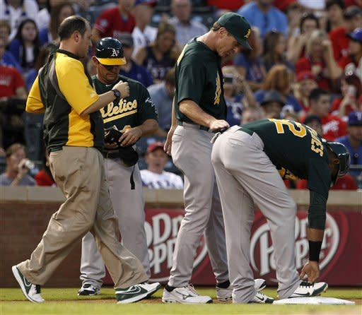 An Oakland Athletics staff member and manager Bob Melvin, center, check on Yoenis Cespedes (52) after Cespedes reached third on a run scoring triple off a pitch from Texas Rangers' Martin Perez in the first inning of a baseball game, Wednesday, Sept. 26, 2012, in Arlington, Texas. Cespedes remained in the game. (AP Photo/Tony Gutierrez)