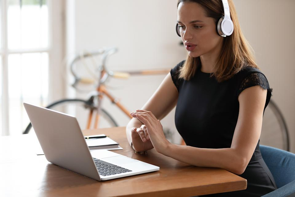 Side view concentrated businesswoman wearing wireless headphones, listening to educational seminar at workplace. Young confident female entrepreneur manager worker holding video call with clients.