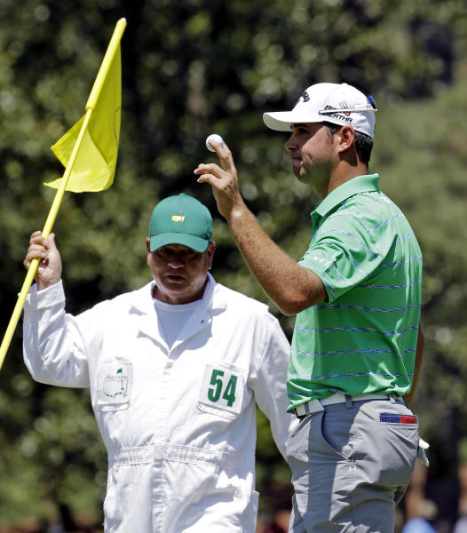 Caddie Tony Navarro looks at Gary Woodland as he holds up his ball after a birdie on the 10th hole during the third round of the Masters golf tournament Saturday, April 12, 2014, in Augusta, Ga. (AP Photo/David J. Phillip)