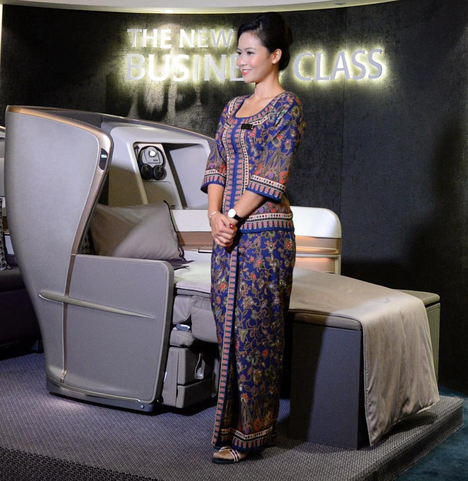A Singapore Airlines (SIA) stewardess stands next to a display of the new Singapore Airlines Business Class seat during their next generation cabin product launch in Singapore on July 9, 2013. SIA on July 9 unveiled new seats and other in-flight amenities as part of a sweeping upgrade of its cabins amid intensifying competition in the industry. AFP PHOTO / ROSLAN RAHMAN
