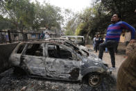 A man stands on a car vandalized in Tuesday's violence in New Delhi, India, Wednesday, Feb. 26, 2020. At least 20 people were killed in three days of clashes in New Delhi, with the death toll expected to rise as hospitals were overflowed with dozens of injured people, authorities said Wednesday. The clashes between Hindu mobs and Muslims protesting a contentious new citizenship law that fast-tracks naturalization for foreign-born religious minorities of all major faiths in South Asia except Islam escalated Tuesday. (AP Photo/Rajesh Kumar Singh)