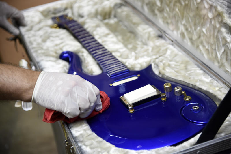 """FILE - In this May 6, 2020 file photo, the """"Blue Angel"""" Cloud 2 electric guitar custom-made for the musician Prince in the 1980s is polished at Julien's Auctions warehouse in Culver City, Calif. On Friday, June 19, 2020, the instrument shot past the top estimate of $200,000 it was expected to fetch at the Music Icons sale at the auction house. (AP Photo/Chris Pizzello)"""