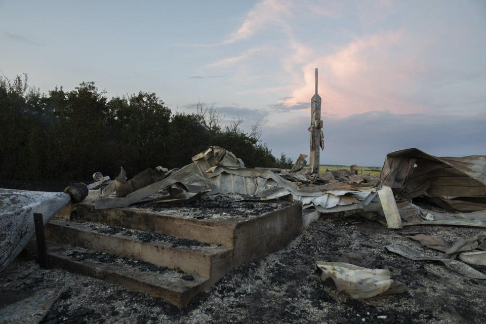 Ashes and debris are all that remains after a fire at a church in Saskatchewan. Debris with sunset in the background