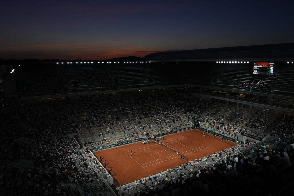 Spain's Rafael Nadal, right, plays Serbia's Novak Djokovic during their semifinal match of the French Open tennis tournament at the Roland Garros stadium Friday, June 11, 2021 at sunset in Paris. (AP Photo/Christophe Ena)