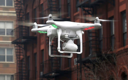 A camera drone operated by a civilian flies near the scene where two buildings were destroyed in an explosion in New York, in this file photo taken March 12, 2014. REUTERS/Mike Segar/Files