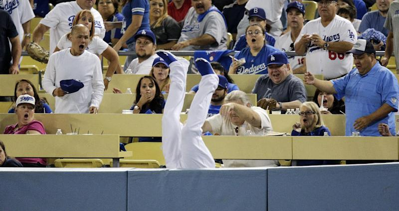 Fans react as Los Angeles Dodgers left fielder Carl Crawford falls upside down over the rail after catching a foul ball hit by Atlanta Braves' Justin Upton during the seventh inning in Game 3 of the National League division baseball series Sunday, Oct. 6, 2013, in Los Angeles. (AP Photo/Jae C. Hong)