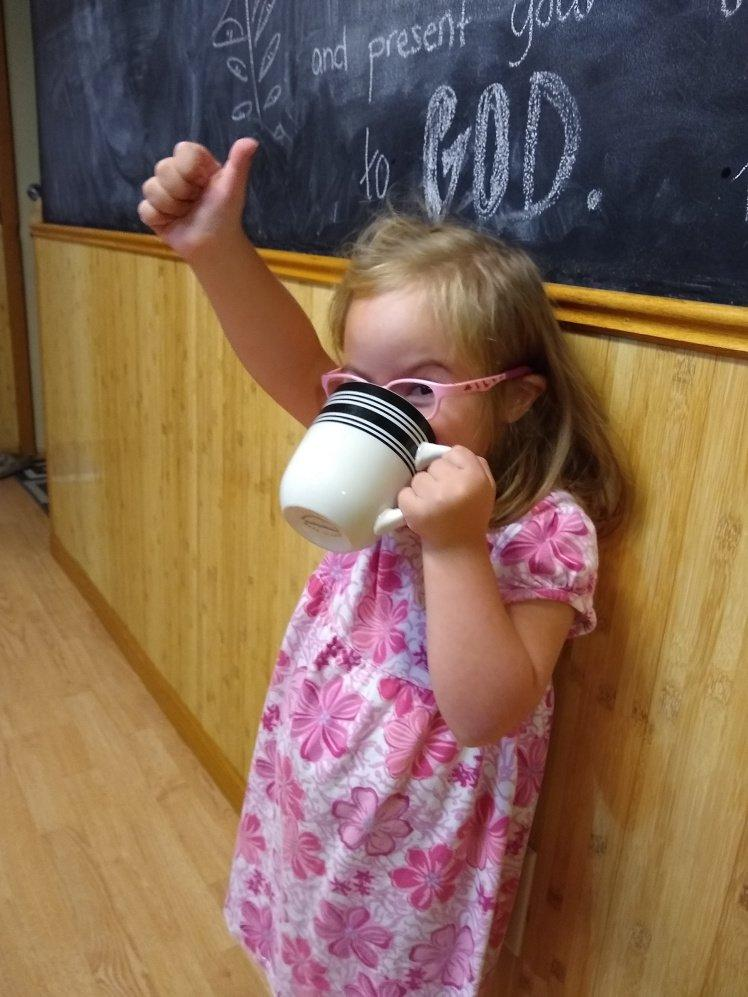 Willow drinking from a mug and giving thumbs up.
