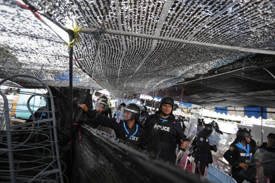 Policemen pull the netting down as they enter an encampment of anti-government protesters during clashes near the Government House in Bangkok February 18, 2014. A Thai police officer was killed and dozens of police and anti-government protesters were wounded in gun battles and clashes in Bangkok on Tuesday, officials and witnesses said. REUTERS/Damir Sagolj (THAILAND - Tags: SOCIETY CIVIL UNREST POLITICS)