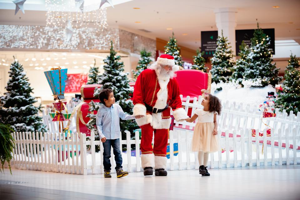 Multi-Ethnic family shops at Shopping Mall during Christmas Time with Santa Claus. Santa Claus and children are walking hand by hand. Photo was taken in Quebec Canada.