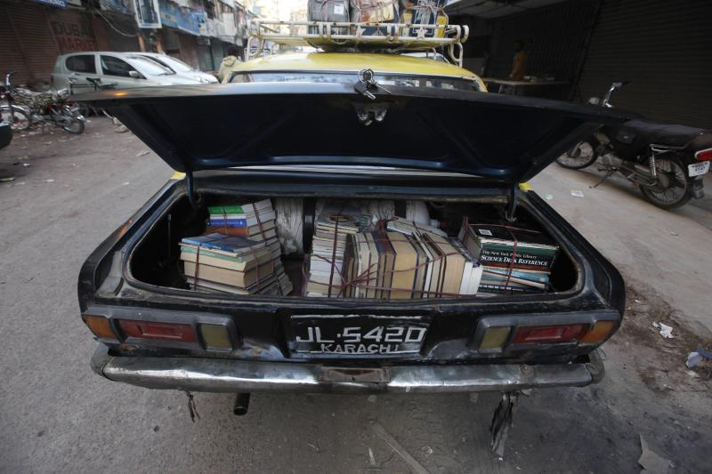 Bundles of second-hand books are placed on the back of taxi, to be brought out to sell, at the Sunday Book Bazaar in Karachi