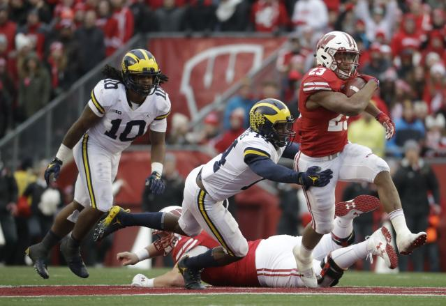 Wisconsin's Jonathan Taylor runs past Michigan's Josh Metellus during the second half of an NCAA college football game Saturday, Nov. 18, 2017, in Madison, Wis. (AP Photo/Morry Gash)